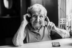 Starsza szczęśliwa kobieta opowiada na telefonie komórkowym Fotografia Stock