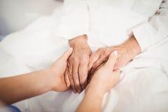 Starsze kobiety i pielęgniarki mienia ręki zdjęcia stock