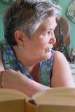 Starsze kobiety z książkowy patrzeć daleko od Obrazy Royalty Free