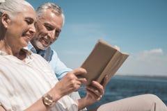 Starsze osoby dobierają się czytelniczą książkę na quay przy dniem Zdjęcia Stock