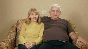 Starsze osoby dobierają się odpoczywać w domu na leżance i patrzeć kamerę Są uśmiechnięci Męża uściśnięcie jego żona zbiory wideo