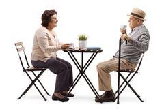 Starsze starsze osoby dobierają się pić kawę przy stołem zdjęcie royalty free
