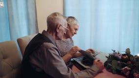 Starsze osoby dobierają się przyglądającego album fotograficznego zdjęcie wideo
