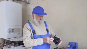 Starsze osoby obsługują być ubranym błękitnych kombinezony trzymają plastikową część od drymby w rękach zdjęcie wideo