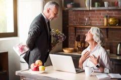 Starsze osoby obsługują dawać kwiaty jego kochana żona obrazy stock