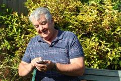 Starsze osoby obsługują texting na jego telefon komórkowy. Zdjęcia Royalty Free
