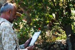 Starsze osoby obsługują używać pastylki, starsza osoba mężczyzna czytelniczego ebook/ fotografia stock