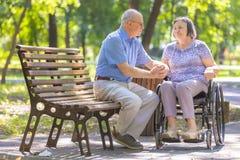 Starsze osoby obsługują umacniają jego żony w wózku inwalidzkim Fotografia Stock