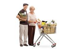 Starsze osoby obsługują z torba na zakupy i kobietą z wózek na zakupy Obrazy Stock