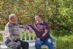 Starsze osoby ojcują i syn na ławce w jesień parku zdjęcia stock