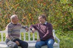 Starsze osoby ojcują i syn na ławce w jesień parku obrazy stock