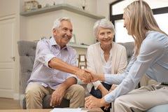 Starsze pary chwiania ręki z pieniężnym advisor obraz stock