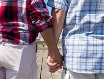 Starsze starsze pary mienia ręki na spacerze na letnim dniu obraz stock