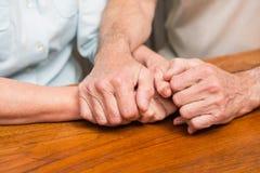 Starsze pary mienia ręki na stole Zdjęcie Stock