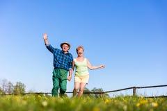Starsze pary mienia ręki outdoors i bieg Fotografia Royalty Free