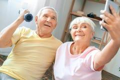 Starsze pary ćwiczenia opieki zdrowotnej selfie fotografie z dumbbell wpólnie w domu Zdjęcie Stock