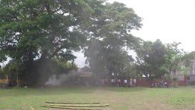 Starsze szkolne chłopiec i dziewczyny znosi odór, wdycha faula dym od płonących banialuk liście i śmieci pod ogromnym drzewem zbiory