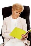 Starsze zadumane skupiać się biznesowej kobiety czytania notatki zdjęcie stock