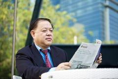 Starszego Azjatyckiego biznesmena czytelnicza gazeta Fotografia Royalty Free