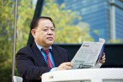 Starszego Azjatyckiego biznesmena czytelnicza gazeta Obrazy Stock