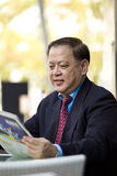 Starszego Azjatyckiego biznesmena czytelnicza gazeta Fotografia Stock