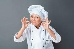 Starszego kobieta szefa kuchni pracowniana pozycja odizolowywająca na szary seans ciszy gesta ono uśmiecha się obraz royalty free