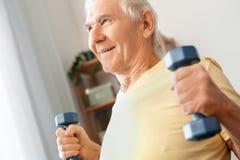 Starszego mężczyzna ćwiczenia opieki zdrowotnej mienia dumbbells zakończenie w domu Obraz Royalty Free