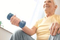 Starszego mężczyzna ćwiczenia opieki zdrowotnej mienia siedzący dumbbell w domu Zdjęcie Royalty Free