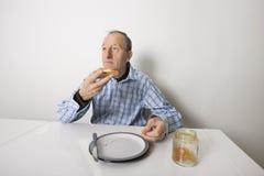 Starszego mężczyzna łasowania chleba rozszerzanie się z cukierki galarety dżemem przy stołem Zdjęcia Royalty Free