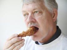 Starszego mężczyzna łasowania pieczonego kurczaka noga Fotografia Stock