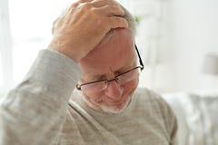 Starszego mężczyzna cierpienie od migreny w domu obraz royalty free