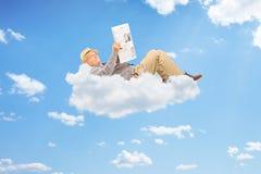 Starszego mężczyzna czytelnicza gazeta i lying on the beach na chmurach Zdjęcie Royalty Free