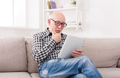 Starszego mężczyzna czytelnicza wiadomość na cyfrowej pastylce Obrazy Stock