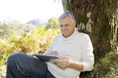 Starszego mężczyzna czytelnicza wiadomość na pastylce outdoors Obrazy Royalty Free