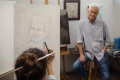 Starszego mężczyzna dopatrywanie podczas gdy artysty rysunek na kanwie Fotografia Royalty Free