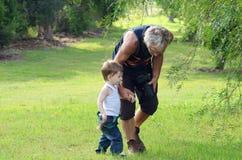 Starszego mężczyzna dziadek odprowadzenie opowiada w parku z wnuk chłopiec zdjęcia stock