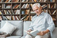 Starszego mężczyzna emerytura pojęcie siedzi czytelniczą książkę w domu fotografia stock