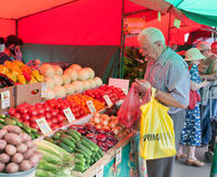 Starszego mężczyzna kupienia warzywa w Jarzynowym jarmarku Zdjęcia Royalty Free