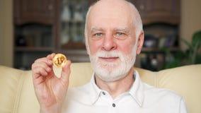 Starszego mężczyzna mienia cryptocurrency bitcoin Błyszczący wirtualny pieniądze online handel Pojęcie savings zbiory