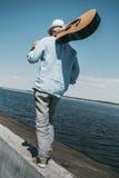 Starszego mężczyzna mienia gitara na ramieniu i odprowadzenie przy quay Zdjęcia Royalty Free