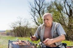 Starszego mężczyzna mienia nóż Podczas gdy Piec na grillu Outside Zdjęcie Royalty Free