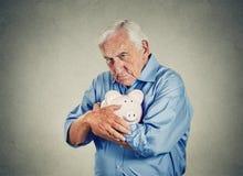Starszego mężczyzna mienia prosiątka bank Obrazy Royalty Free