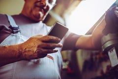 Starszego mężczyzna mienia wisząca ozdoba i czytelniczy tekst clo zdjęcie stock