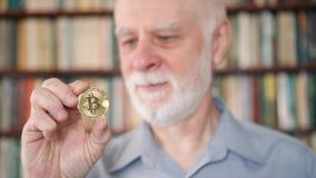Starszego mężczyzna mienie i patrzeć cryptocurrency bitcoin Błyszczący wirtualny pieniądze online handel zdjęcie wideo