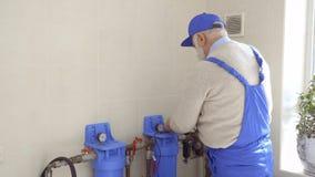 Starszego mężczyzna naprawy ogrzewania drymby w błękitnych kombinezonach zdjęcie wideo