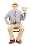 Starszego mężczyzna obsiadanie na krzesła i mienia trofeum Fotografia Royalty Free