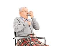 Starszego mężczyzna oddychanie przez jego inhalatoru fotografia royalty free