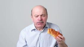 Starszego mężczyzny łasowania cukierki zasycha z gniewną twarzą zbiory