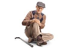 Starszego mężczyzny obsiadanie na mieniu i podłodze jego kolano zdjęcia royalty free