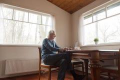 Starszego mężczyzny obsiadanie przy biurkiem pracuje na komputerze obraz royalty free